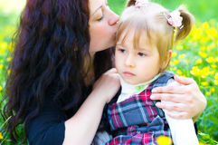 Mother kisses daughter. On the meadow Stock Photos