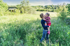 Mother kisses daughter in nature Royalty Free Stock Images