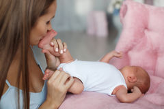 The mother kisses the feet of a newborn son. Young beautiful brunette women with long straight hair, dressed in a white sundress, spending time with his newborn Royalty Free Stock Photos