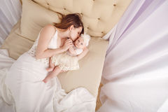 Mother kisses the firstborn, lying on sofa. Stock Photo