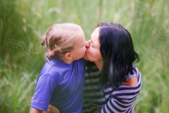 The mother kisses her daugther Stock Image