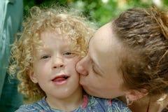Mother kisses her little boy Stock Photo