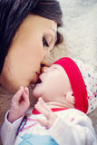 Mother kisses her newborn lying Stock Photos