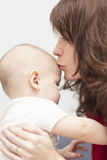Mother kisses her newborn son. Young mother kisses her son and cares about him Stock Photos