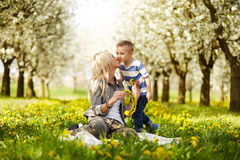 Mother kisses her son. In blooming orchard Royalty Free Stock Photos
