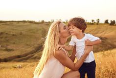 A mother kisses her son in nature in the summer.  stock image
