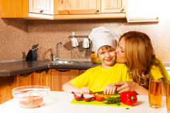 Mother kisses son when he cuts vegetables. Mother kisses her son who is wearing toque as chef cooker while cutting vegetables on the table in the kitchen Royalty Free Stock Photography