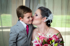 Mother Kisses Son On Her Wedding Day. A young bride kisses her son on her wedding day in her pre-wedding portrait.  She holds her bouquet and he leans in for a Stock Photo