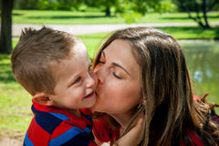 Mother Kisses Son. A mother kisses her young son on the check as he hugs her neck Stock Images