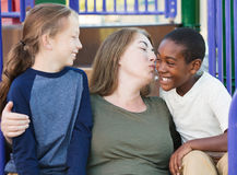 Mother kissing adopted son on cheek. Single mother kissing her adopted son on cheek at park Stock Photo