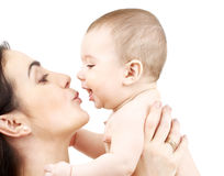 Mother kissing adorable baby. Family, parenting and child care concept - happy mother kissing adorable baby Royalty Free Stock Images