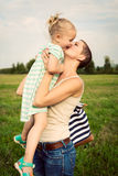 Mother kissing adorable smiling daughter. Happy family, mother kissing adorable smiling daughter Stock Photo