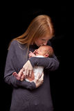Mother kissing baby. Mother holding her baby son and kissing his forehead Royalty Free Stock Image