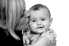 Mother is kissing baby Stock Images