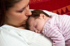 Mother kissing baby asleep Royalty Free Stock Image