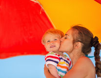 Mother kissing baby on beach under umbrella Stock Photo