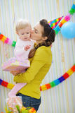 Mother kissing baby on birthday celebration party Stock Photos