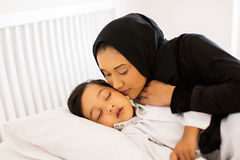 Mother kissing baby boy. Caring muslim mother kissing baby boy while he is asleep Royalty Free Stock Photography
