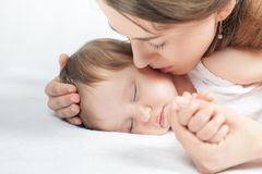 Mother kissing a baby. Care concept. Protection. Healthy sleep. Healthcare. Medical. Mother's care is most important in baby live. White background Royalty Free Stock Photography