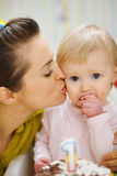 Mother kissing baby eating birthday cake Royalty Free Stock Image
