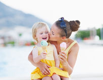 Mother kissing baby while eating ice cream Royalty Free Stock Image