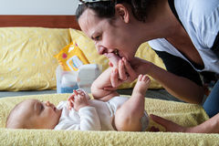 Mother kissing baby feet. On a yellow changing table Stock Photo