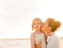 Mother kissing baby girl on beach at the evening Royalty Free Stock Photography
