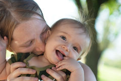 Mother kissing baby girl in her neck Stock Photos