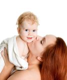Mother kissing baby girl in a towel after bathing. Isolated on white royalty free stock photo