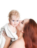 Mother kissing baby girl in a towel after bathing. Isolated on white stock image