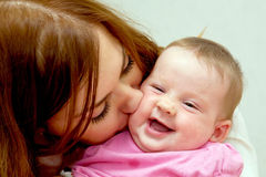 Mother kissing baby, kid laughing. Royalty Free Stock Image