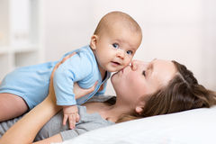 Mother kissing baby lying on bed in nursery Stock Photos