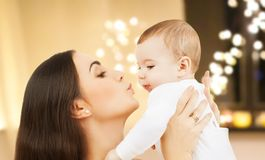 Mother kissing baby over christmas lights royalty free stock image