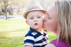 Mother Kissing Baby Son with Surprised Expression. A mother kissing her son on the cheek. They are outside on a sunny warm day. The boy is wearing a straw hat Royalty Free Stock Photos