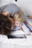 Mother kissing baby watching tablet. Brunette women mother kissing eighteen month aged blonde baby reading digital tablet on white bed Royalty Free Stock Photos