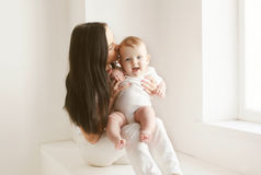 Mother kissing baby in white room at home Stock Images