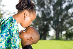 Mother kissing child. Happy african mother kissing child boy Stock Image