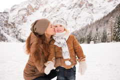 Mother kissing child outdoors among snow-capped mountains Stock Photo