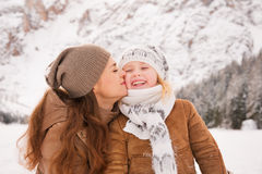 Mother kissing child outdoors among snow-capped mountains Royalty Free Stock Image