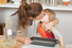 Mother kissing child ready to baking cake Royalty Free Stock Photography