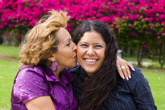 Mother kissing daughter. Senior woman kissing adult daughter with colorful flowers in background Stock Photo