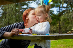 Mother kissing daughter drawing colors park Stock Photo