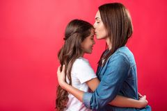 Mother kissing daughter in forehead. Isolated on red Royalty Free Stock Photos