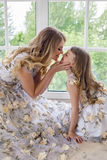 Mother kissing daughter in matching dresses. Sitting by the large window on the floor of the house Stock Photo