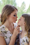 Mother kissing daughter in matching dresses stock photography