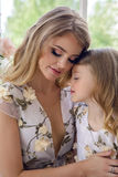 Mother kissing daughter in matching dresses. Sitting by the large window on the floor of the house Royalty Free Stock Images