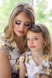 Mother kissing daughter in matching dresses. Sitting by the large window on the floor of the house Royalty Free Stock Photos