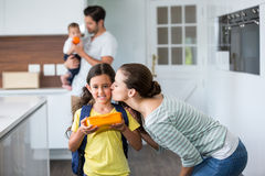 Mother kissing daughter wearing school bag. At home Royalty Free Stock Image