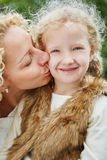 Mother kissing daugther with love Stock Photos