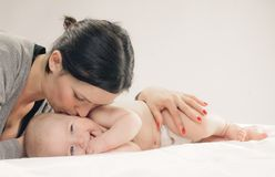 Mother kissing happy baby on cheek Royalty Free Stock Images
